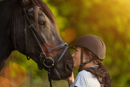 Young Woman kissing her horse at sunrise. Banque d'images