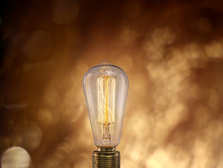 Vintage light bulb on dark background with empty space for text. Banco de Imagens