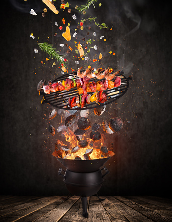 Kettle grill with hot briquettes, cast iron grate and tasty skewers flying in the air. Stock Photo - 101232421