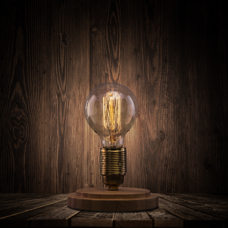 Vintage Edison light bulb on dark background with empty space for text. Banco de Imagens