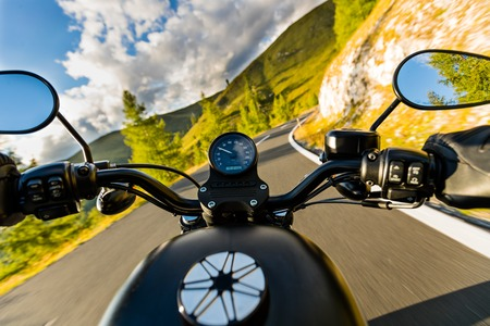Motorcycle driver riding in Alpine highway, handlebars view, Austria, Europe. Stok Fotoğraf
