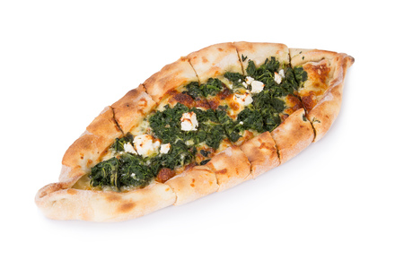 Traditional turkish pizza pide with spinach isolated on white. Top view.