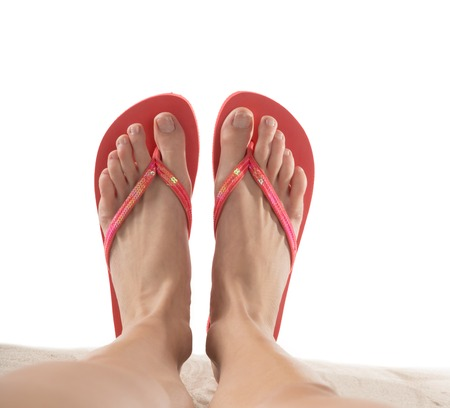 Female legs with flip-flops isolated on white background.