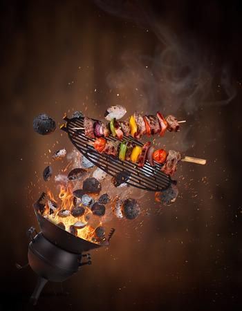Griglia bollitore con bricchette calde, griglia in ghisa e gustosi spiedini che volano in aria. Congelare il concetto di barbecue in movimento. Archivio Fotografico
