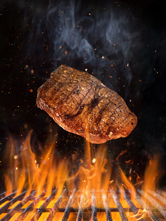 Tasty beef steak flying above cast iron grate with fire flames. Freeze motion barbecue concept.