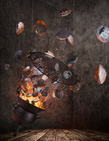Kettle grill with hot briquettes and cost iron grid flying in the air.