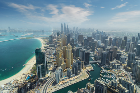 Aerial view of modern skyscrapers and sea in the background in Dubai, UAE.
