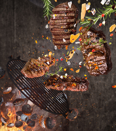 Kettle grill with hot briquettes, cast iron grate and tasty meats flying in the air.