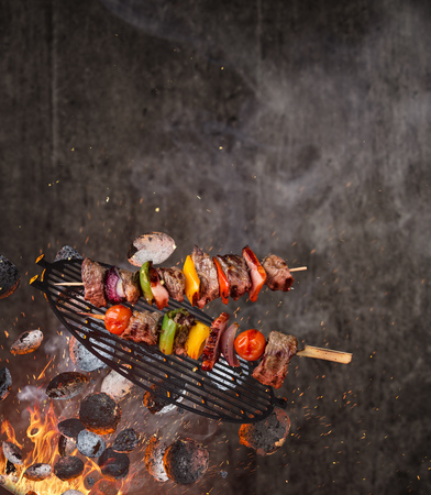 Kettle grill with hot briquettes, cast iron grate and tasty skewers flying in the air.