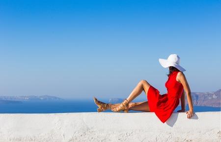 mujer morena en vestido rojo visitando el famoso pueblo blanco de Oia. Foto de archivo