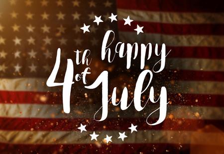 Inscripción feliz 4 de julio con la bandera de Estados Unidos. Foto de archivo