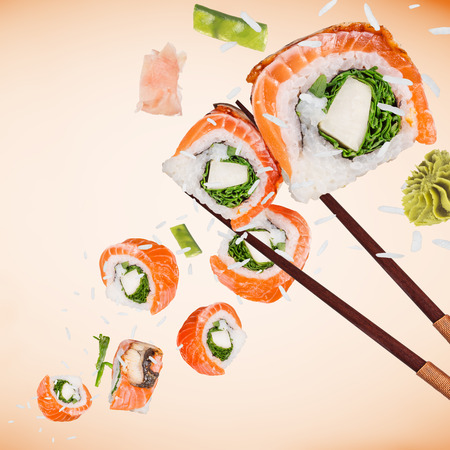 Pieces of delicious japanese sushi frozen in the air on pastel color background. Standard-Bild - 103875330