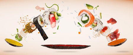 Pieces of delicious japanese sushi frozen in the air on pastel color background. Standard-Bild - 103875344