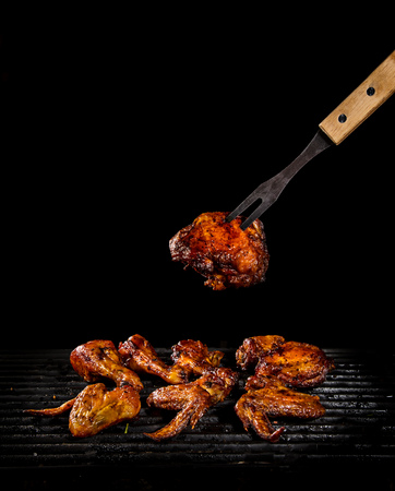 Chicken legs and wings on the grill with flames 版權商用圖片 - 103988514