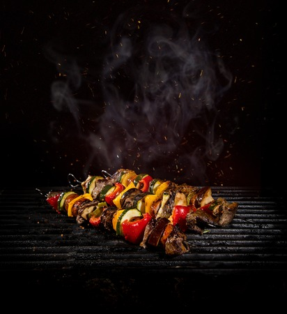 Tasty chicken skewers on iron cast grate with fire flames. 스톡 콘텐츠