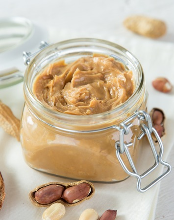 Glass jar with peanut butter on wooden background, close-up.
