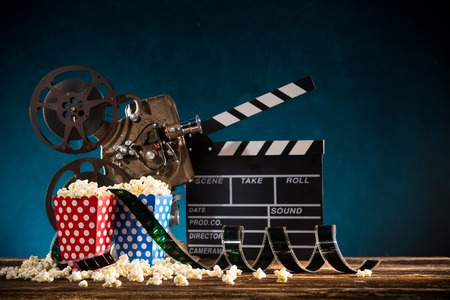 Cinema concept of vintage film reel with popcorn.