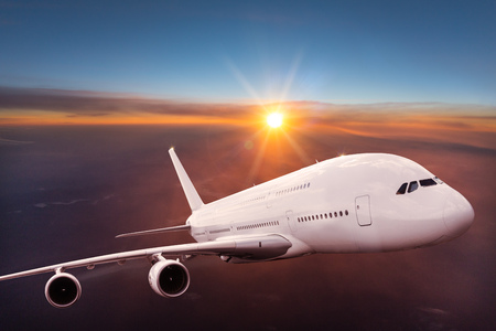 Big commercial airplane flying above dramatic clouds during sunset.