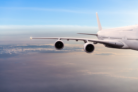 Big commercial airplane flying above dramatic clouds.