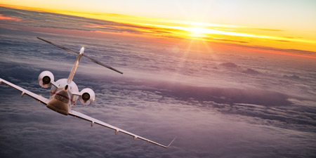 Private jet plane flying above dramatic clouds. Stock Photo