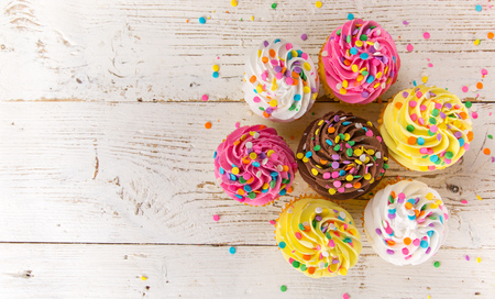 Colorful cup cakes on wooden background.