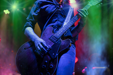 A rocker is playing guitar on stage.