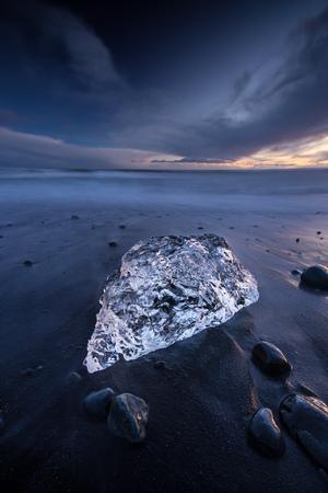 Icebergs dans le lac glaciaire de Jokulsarlon pendant le coucher du soleil, l'Islande