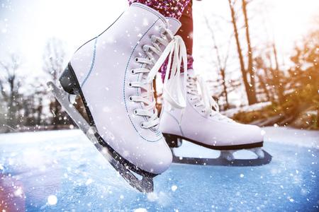 Primer plano de mujer patinaje sobre hielo en un estanque.