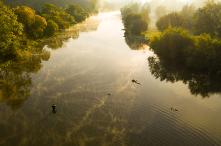 Aerial shot of a man fly fishing in a river during summer morning.
