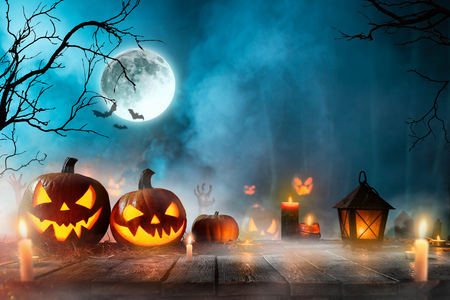 Halloween pumpkins on dark spooky forest with blue fog in background.