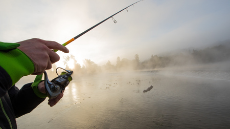 Man fishing in river with fly rod during summer morning. Beautiful fog.
