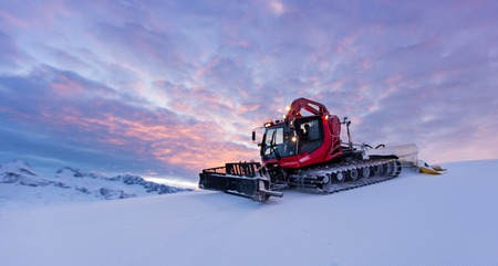 Snowplow machine at snowy ski resort during sunset Stock Photo