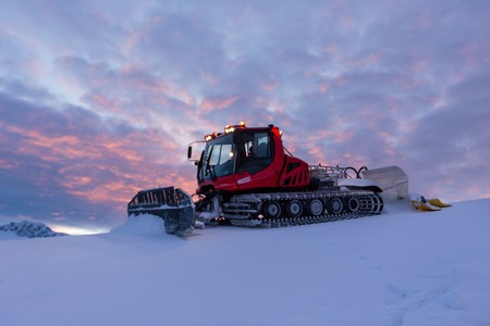 Snowplow machine at snowy ski resort during sunset