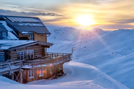 Beautiful winter panorama with wooden mountain cabin. Alpine background.