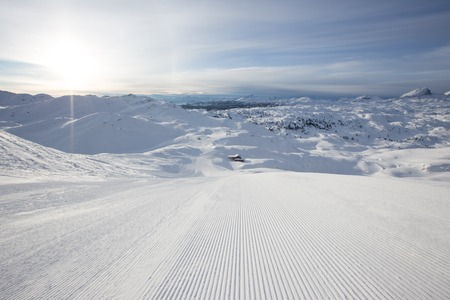 Beautiful winter panorama with fresh powder snow on ski slope. Alpine mountains background.