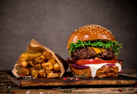 Tasty burger with french fries on wooden table. Фото со стока