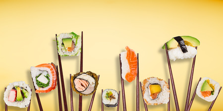 Traditional japanese sushi pieces placed between chopsticks Foto de archivo