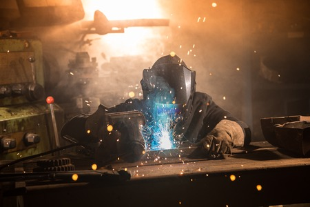 Welder is welding metal part in factory Stock Photo