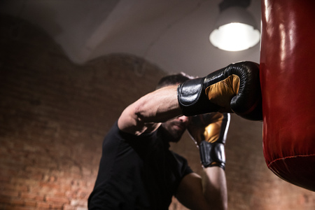 Hand of boxer at the moment of impact on punching bag.