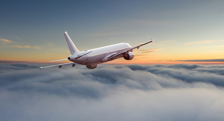 Commercial airplane jetliner flying above dramatic clouds. Stock Photo