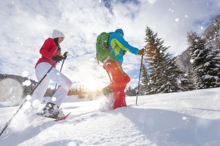 Sneeuwschoenwandelaars die in poedersneeuw lopen met prachtig zonsopganglicht.