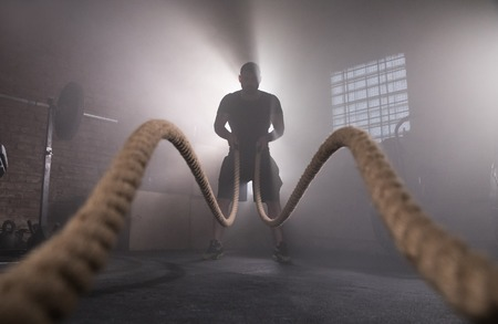 Silhouette of man working out with battle ropes at gym. Imagens