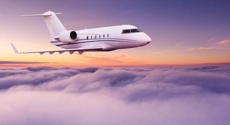 Kleines privates Düsenflugzeug, das über schöne Wolken fliegt. Standard-Bild