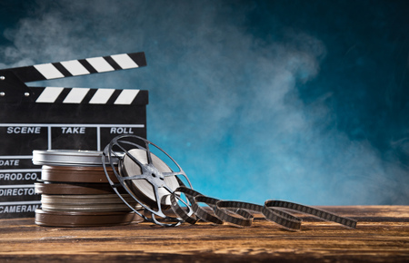Cinema concept of vintage film reel with popcorn on old wooden background. Stock Photo