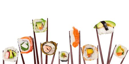 Piezas de sushi japonés tradicional colocados entre palillos, separados sobre fondo blanco.