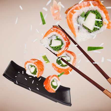 Pieces of delicious japanese sushi frozen in the air. Standard-Bild - 119166795