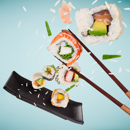 Pieces of delicious japanese sushi frozen in the air. Standard-Bild - 119167049