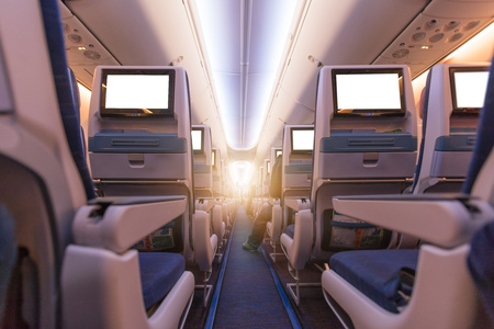 Comfortable seats in cabin of aircraft with screens in chairs back