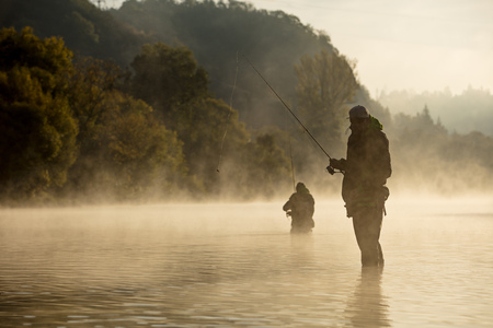 Men fishing in river with fly rod during summer morning. Banco de Imagens