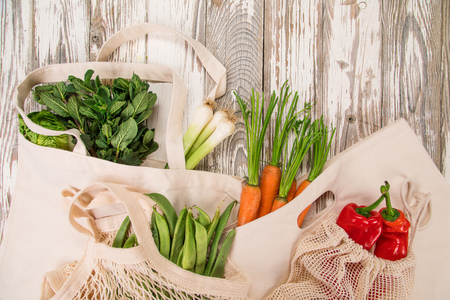Fresh vegetables in bio eco cotton bags on old wooden table. Zero waste shopping concept. Stok Fotoğraf